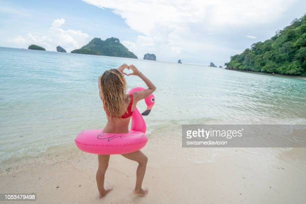young woman making heart shape finger frame on idyllic beach with inflatable flamingo in the islands of thailand. people travel destinations fun and cool attitude concept - flamingo heart stock pictures, royalty-free photos & images