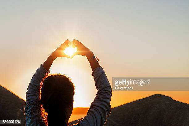 young woman making heart shape with hands at sunset outdoors