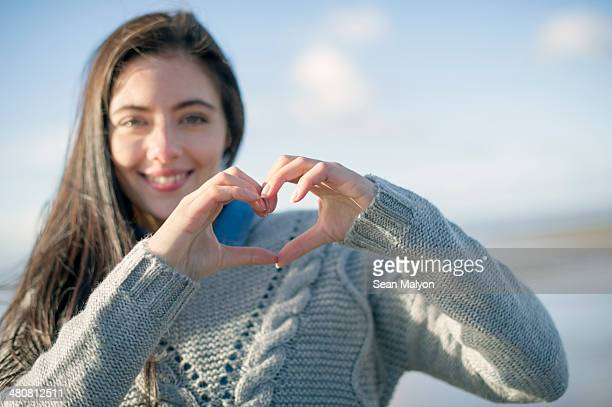young woman making heart shape with hands - sean malyon stock pictures, royalty-free photos & images