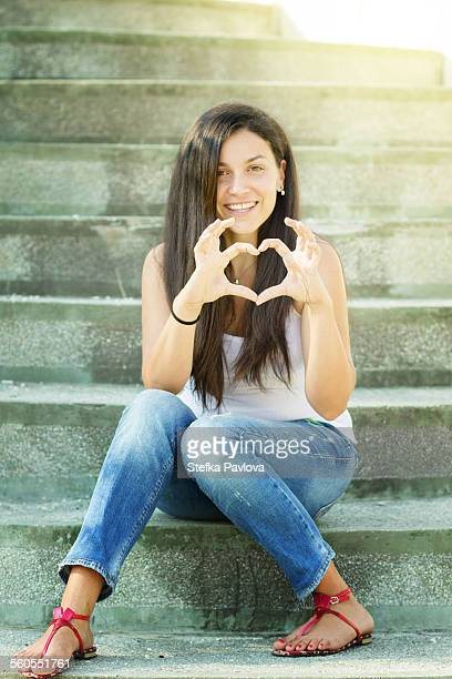 Young woman making heart shape with hands