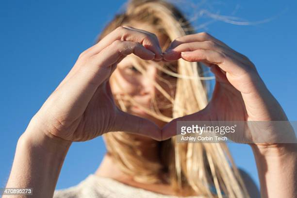 Young woman making heart sign with hands, Breezy Point, Queens, New York, USA