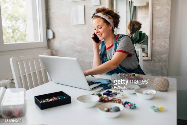 young woman making jewelry and selling it online - selling stock pictures, royalty-free photos & images