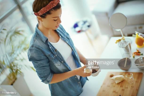 junge frau, die natürliche bio-gesichtscremes in ihrem shop. - etwas herstellen stock-fotos und bilder