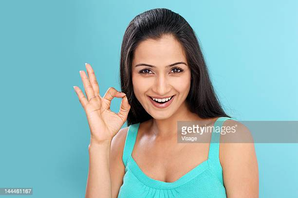 A young woman making OK gesture