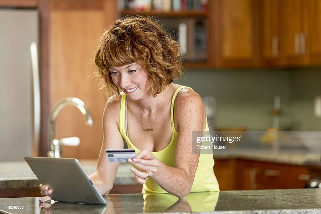 Young woman making online purchase in her kitchen : Stockfoto