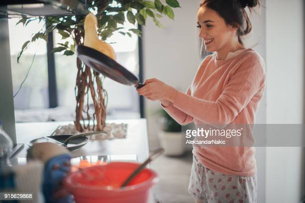 young woman making pancakes - pancake stock pictures, royalty-free photos & images
