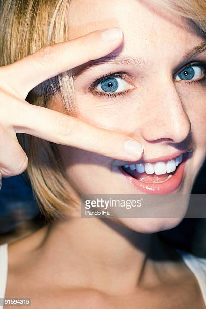 Young woman making peace sign, laughing, close-up