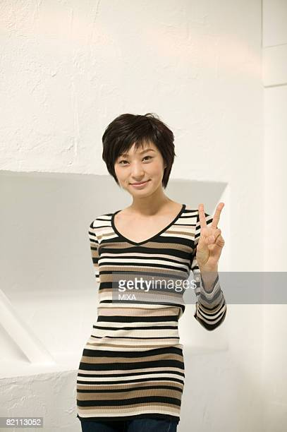 Young woman making peace sign