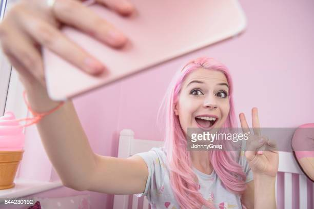 Young woman making peace sign posing towards smartphone in bedroom