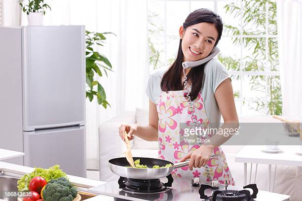 Young woman making phone call and cooking in kitchen