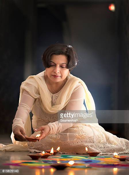 Young Woman making Rangoli, decorating with Oil lamps for Diwali