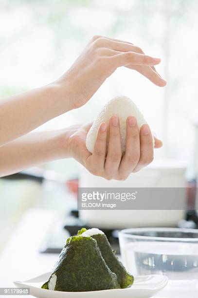 Young woman making rice ball