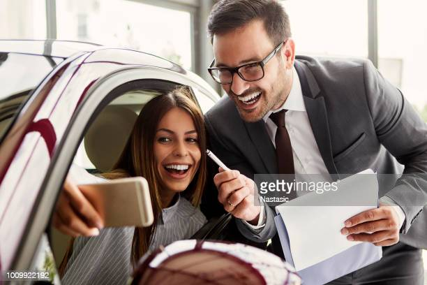 young woman making selfie with car salesman - car salesperson stock pictures, royalty-free photos & images