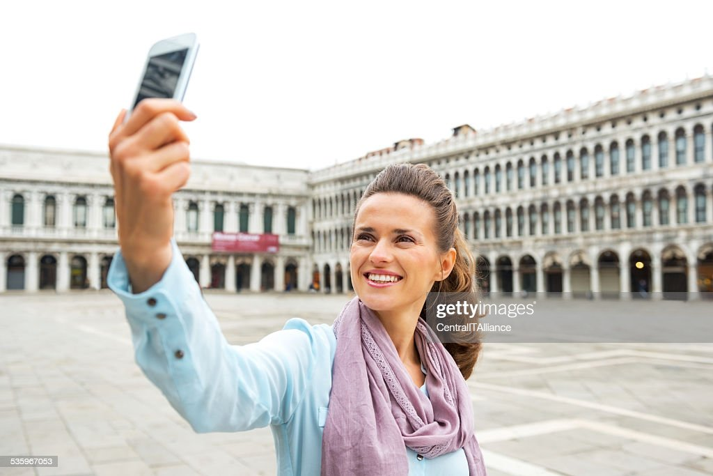 Young woman making selfie with cell phone in venice, italy : Stock Photo