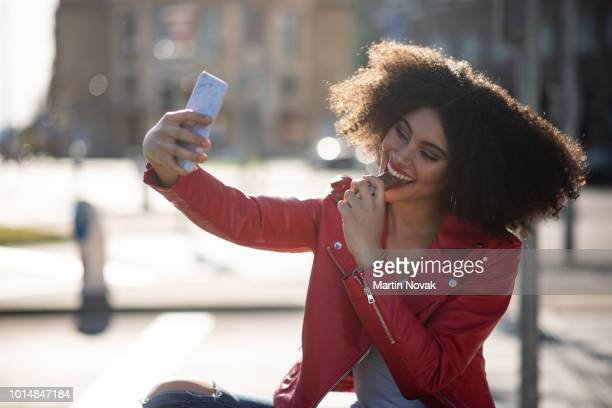 Young woman making selfie with chocolate