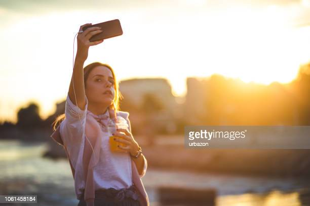 young woman making selfies and listening to music by the river - mp3 juices stock photos and pictures