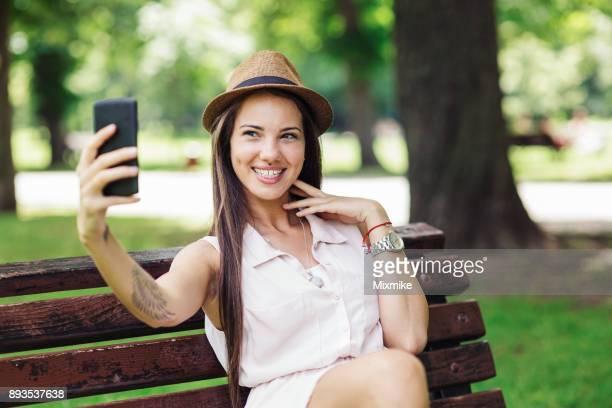 young woman making selfies in the park. - vanity stock pictures, royalty-free photos & images