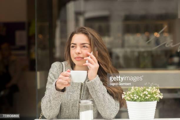 young woman making smartphone call from sidewalk cafe - sigrid gombert imagens e fotografias de stock