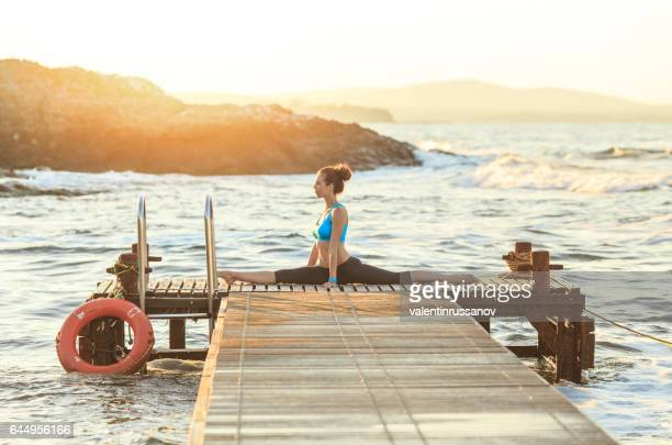 Junge Frau macht Spagat auf einem pier
