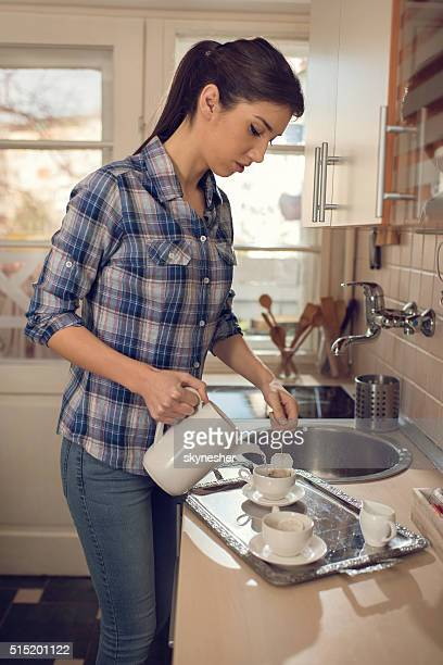 Young woman making tea in the kitchen.