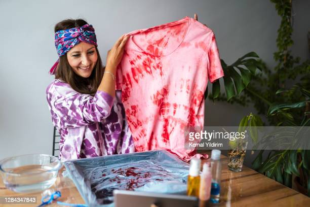 young woman making tie dye at living room - middle east stock pictures, royalty-free photos & images