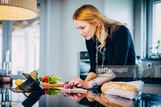 Young woman making vegetable soup