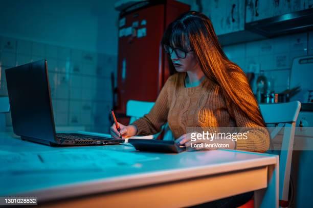 mujer joven gestiona las finanzas del hogar - henri coste fotografías e imágenes de stock