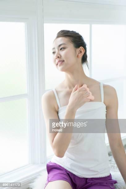 young woman massaging her chest - cami fotografías e imágenes de stock