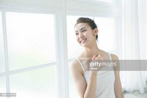 Young woman massaging her chest