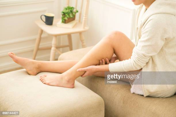 young woman massaging her leg in room - massage rooms photos et images de collection