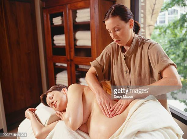 young woman massaging pregnant woman in beauty parlour - massage parlour stock photos and pictures