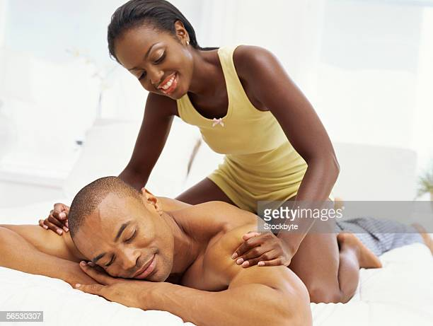 young woman massaging the back of a young man