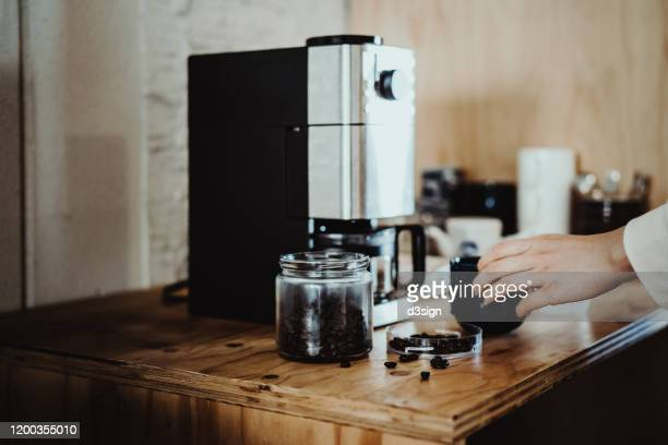 young woman measuring and pouring roasted coffee beans into coffee machine and preparing coffee at home in the early morning - coffee maker stock pictures, royalty-free photos & images