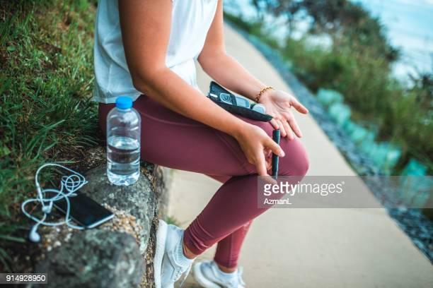 joven, medir nivel de azúcar en la sangre después del entrenamiento - diabetes fotografías e imágenes de stock