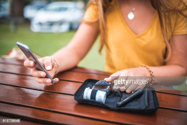 Young woman measuring blood sugar level and using mobile phone