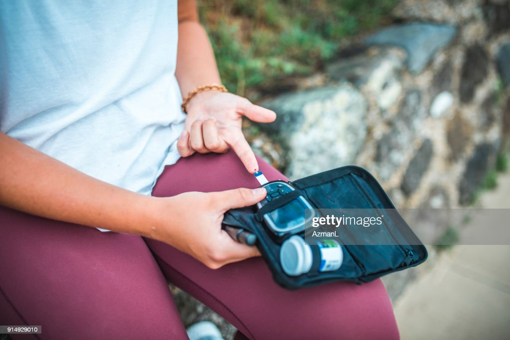 Young woman measuring blood sugar level : Stock Photo