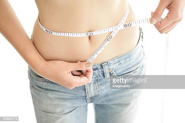a young woman measuring her waist with the help of a measure tape - centimetre stock photos and pictures