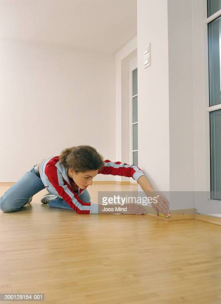Young woman measuring skirting board in empty room