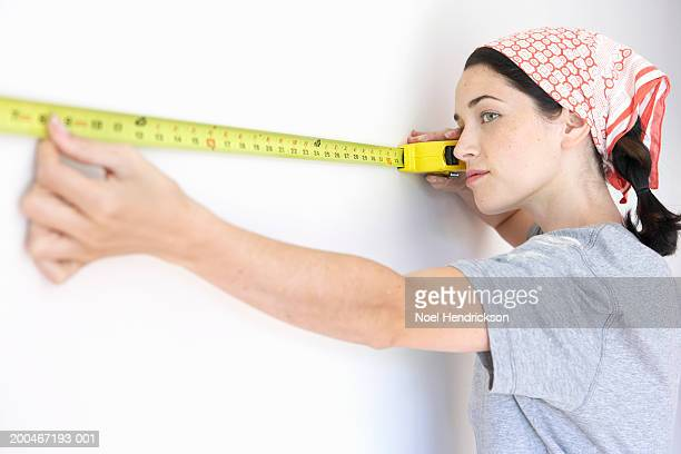 Young woman measuring wall with tape measure, side view