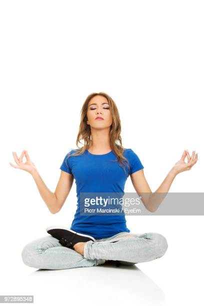 young woman meditating against white background - cross legged stock pictures, royalty-free photos & images