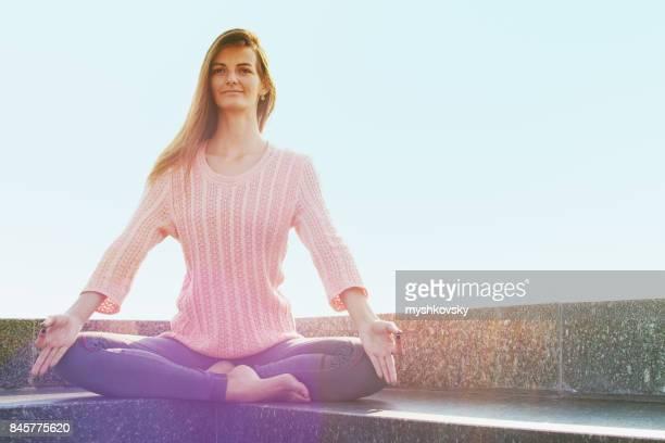 Young woman meditating at dawn