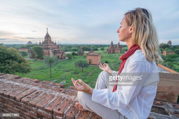 Young woman meditating at the Bagan archeological zone at sunrise, Myanmar