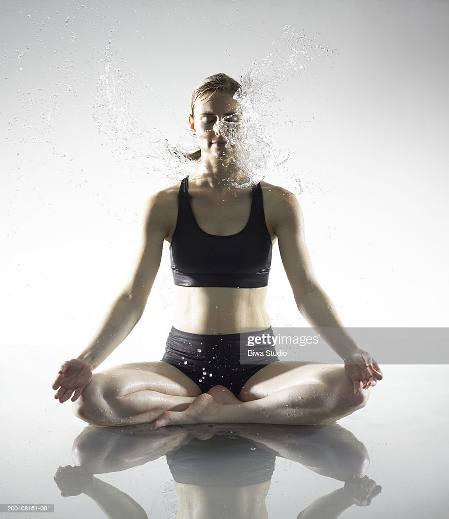 Young woman meditating being splashed with water : ストックフォト