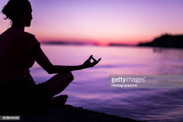 young woman meditating by peaceful sea - purple stock pictures, royalty-free photos & images