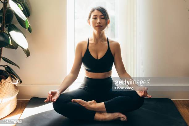 young woman meditating in a yoga pose - buddhism stock pictures, royalty-free photos & images