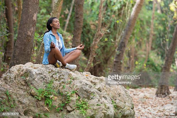 Young woman meditating in forest.