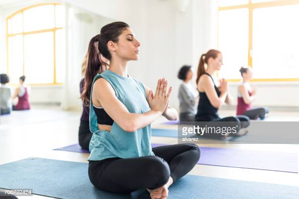 Young woman meditating in health club