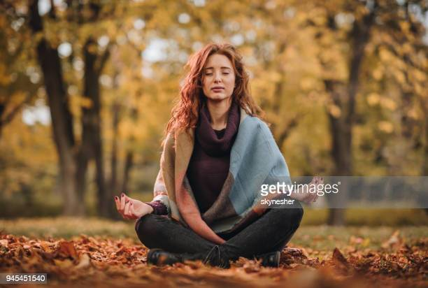 young woman meditating in lotus position at the park. - spirituality stock pictures, royalty-free photos & images