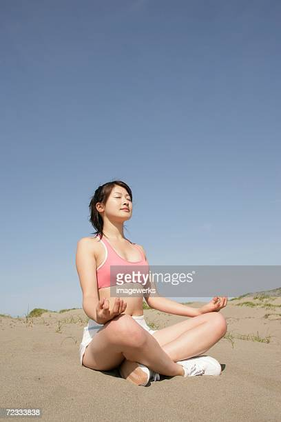 a young woman meditating in the desert - ブラトップ ストックフォトと画像