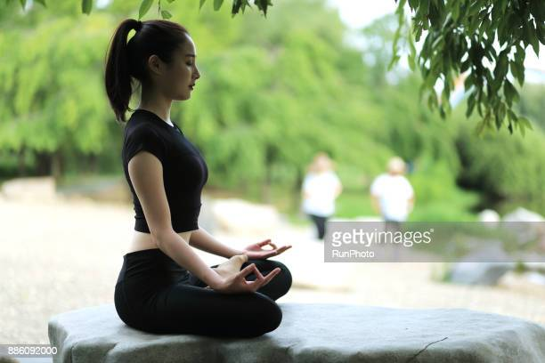 Young woman meditating in the park, eyes closed